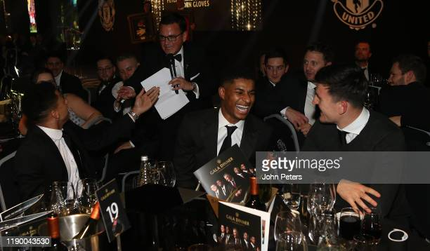Jesse Lingard, Marcus Rashford and Harry Maguire of Manchester United bid for an auction item at the annual Manchester United UNICEF Dinner at Old...