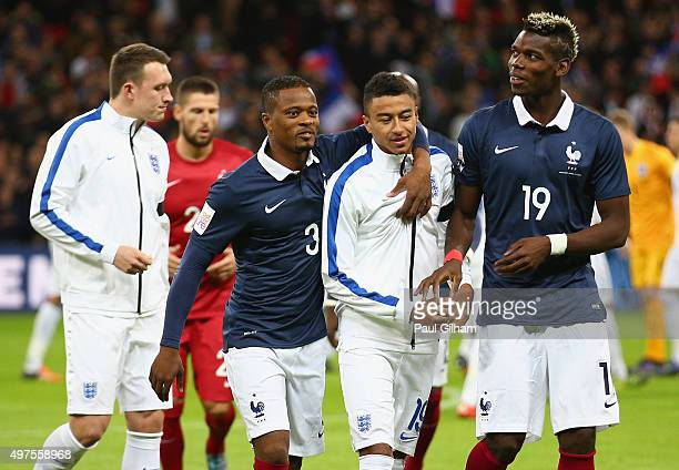 Jesse Lingard of England is greeted by Patrice Evra and Paul Pogba of France prior to the International Friendly match between England and France at...