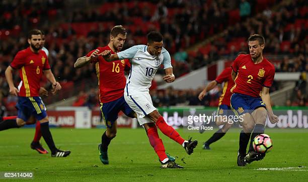Jesse Lingard of England shoots past Cesar Azpilicueta of Spain during the international friendly match between England and Spain at Wembley Stadium...
