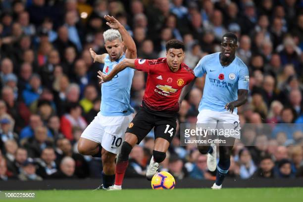 Jesse Lingard of Manchester United is challenged by Sergio Aguero of Manchester City and Benjamin Mendy of Manchester City during the Premier League...