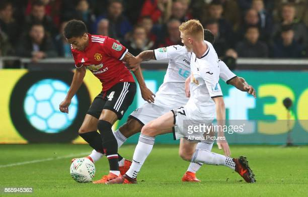 Jesse Lingard of Manchester United is challenged by Wayne Routledge of Swansea City and Sam Clucas during the Carabao Cup Fourth Round match between...
