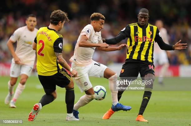 Jesse Lingard of Manchester United is tackled by Daryl Janmaat and Abdoulaye Doucoure of Watford during the Premier League match between Watford FC...
