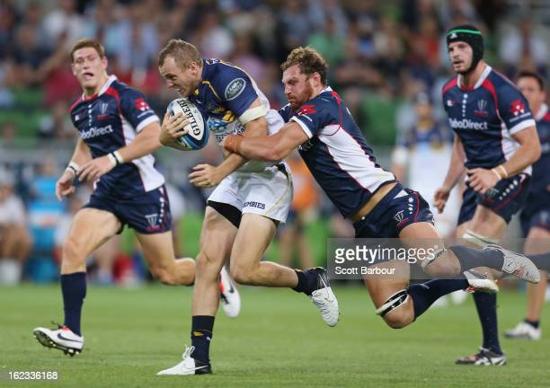Jesse Mogg of the Brumbies is tackled by Scott Higginbotham of the Rebels as he makes a break which led to a try during the round two Super Rugby...