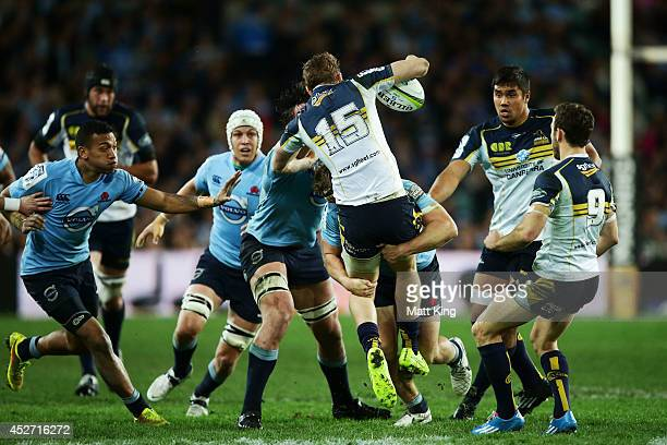 Jesse Mogg of the Brumbies is tackled heavily by Michael Hooper of the Waratahs during the Super Rugby Semi Final match between the Waratahs and the...