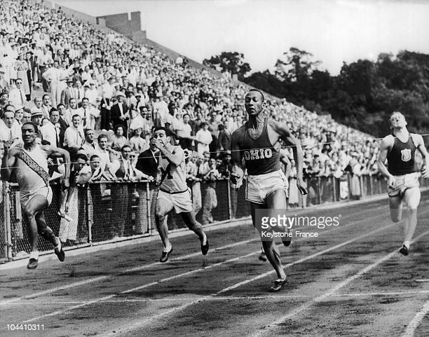 Jesse OWENS in lead and breasting the tape is in center Ralph Harold METCALFE in second place on inside Sam STOLLER of Michigan in third place is...