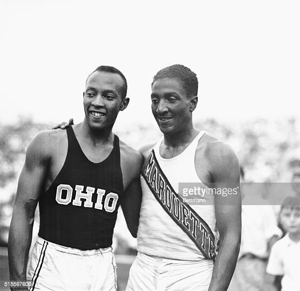 Jesse Owens of Ohio State and Ralph Metcalfe of the Marquette Club after they had finished in onetwo order respectively in the 100 meter event at the...