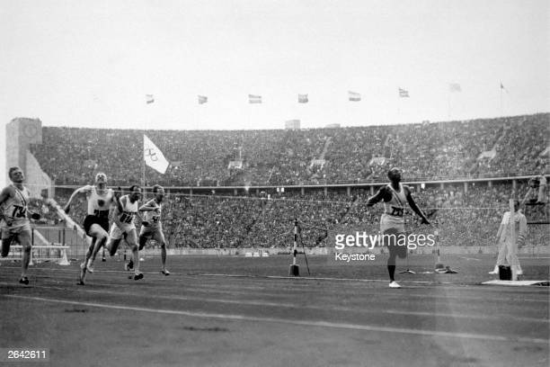 Jesse Owens of the USA crosses the finishing line to win the 100 metres at the 1936 Olympics in Berlin He won three other gold medals in the 200...