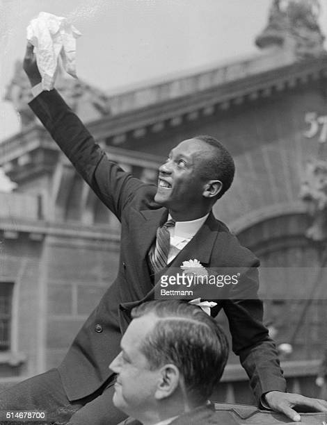 Jesse Owens sensational track star of the Olympic games waving to crowds during the 'tickertape' parade up Manhattan in honor of the Olympic athletes...