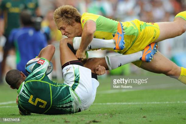 Jesse Parahi of Australia tackles Cornal Hendricks during the Gold Coast Sevens Cup semi final match between Australia and South africa at Skilled...