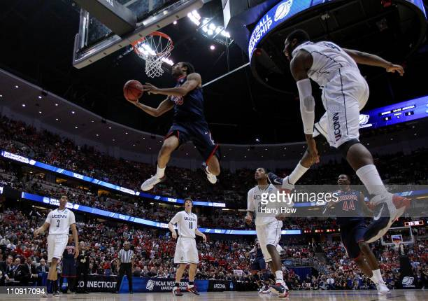Jesse Perry of the Arizona Wildcats goes to the basket Alex Oriakhi of the Connecticut Huskies during the west regional final of the 2011 NCAA men's...