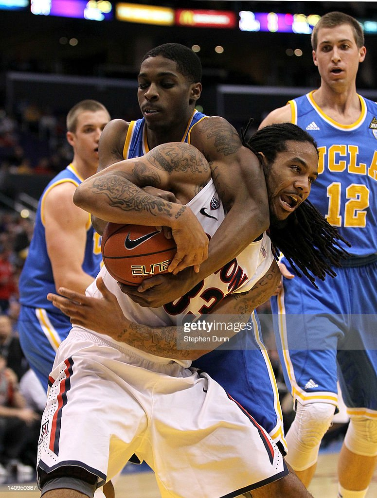 Jesse Perry #33 of the Arizona Wildcats is grabbed from behind by Lazeric Jones #11 of the UCLA Bruins in the second half during the quarterfinals of the 2012 Pacific Life Pac-12 basketball tournament at Staples Center on March 8, 2012 in Los Angeles, California.