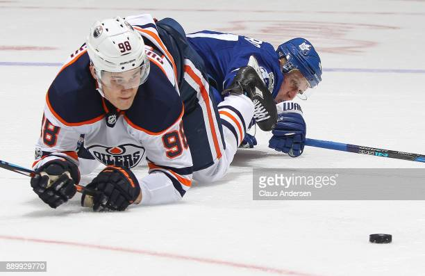 Jesse Puljujarvi of the Edmonton Oilers battles against Leo Komarov of the Toronto Maple Leafs during an NHL game at the Air Canada Centre on...