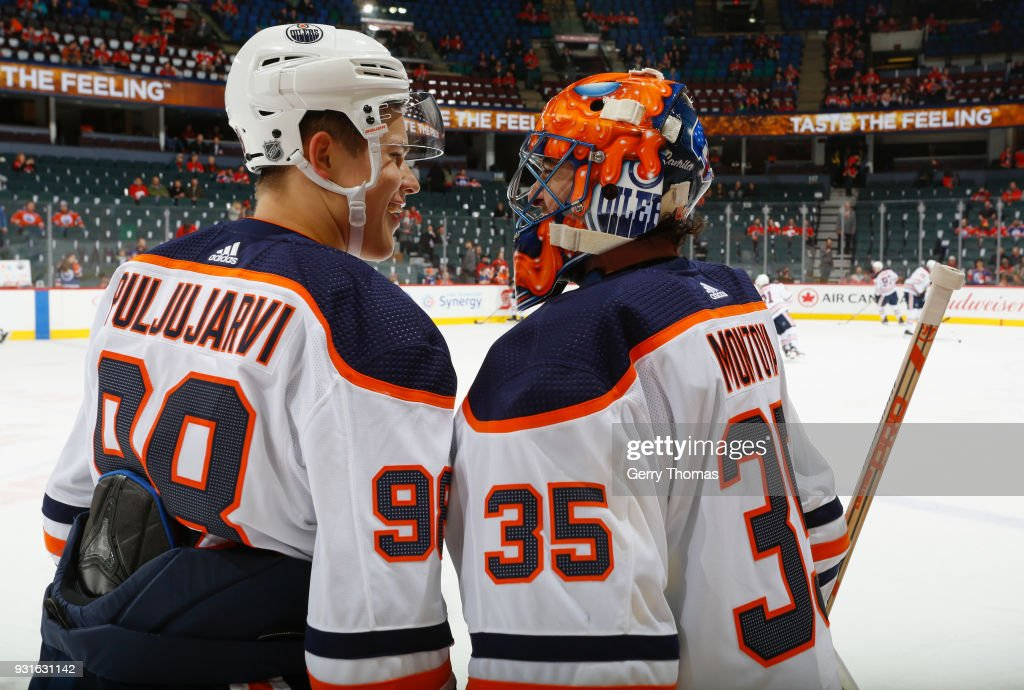 Jesse Puljujarvi #98 of the Edmonton Oilers chats during warm up with teammate Al Montoya #35 prior to puck drop against the Calgary Flames at Scotiabank Saddledome on March 13, 2018 in Calgary, Alberta, Canada.