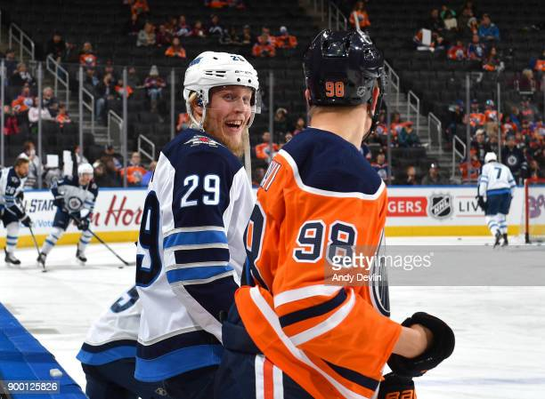 Jesse Puljujarvi of the Edmonton Oilers exchanges word with Patrik Laine of the Winnipeg Jets on December 31 2017 at Rogers Place in Edmonton Alberta...