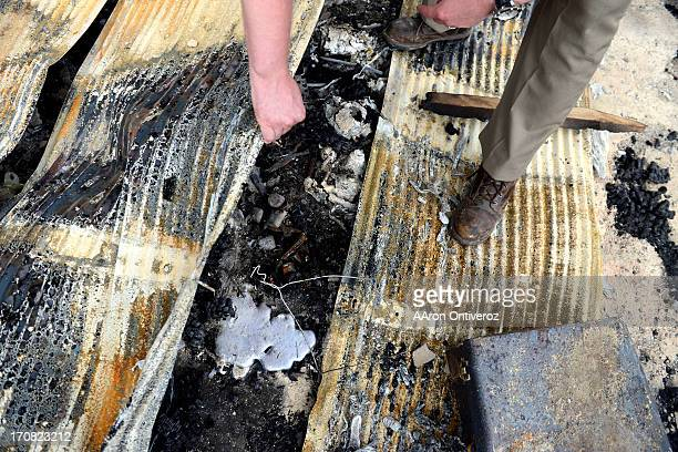 Jesse Russow looks at a puddle of aluminum that was formerly a set of rims as he surveys the damage of his rental property which was the southernmost...