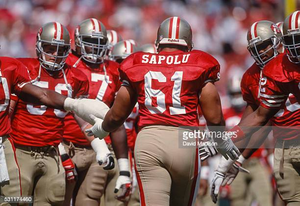 Jesse Sapolu of the San Francisco 49ers is greeted by his teammates prior to a National Football League game against the Buffalo Bills played on...