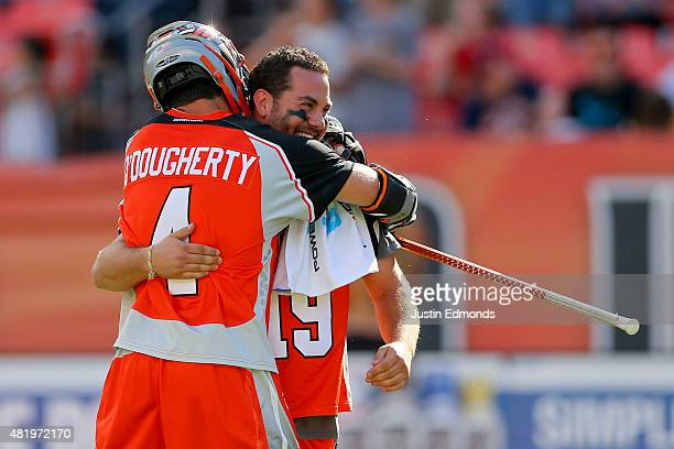 Jesse Schwartzman of the Denver Outlaws gets a hug from Chris O'Dougherty after playing in his final game following their 1514 overtime win against...