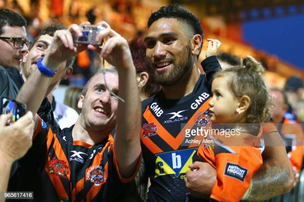 Jesse SeneLefao of Castleford Tigers poses for a photo with a fan during the Roger Millward Trophy match between Hull KR and Castleford Tigers as...