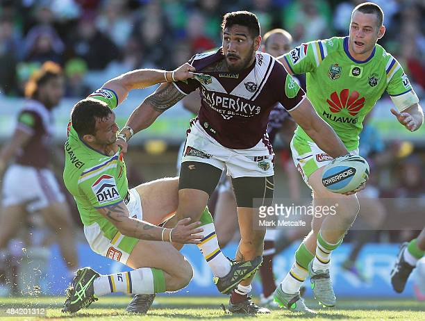 Jesse SeneLefao of the Sea Eagles fends off the tackle of Josh Hodgson of the Raiders during the round 23 NRL match between the Canberra Raiders and...