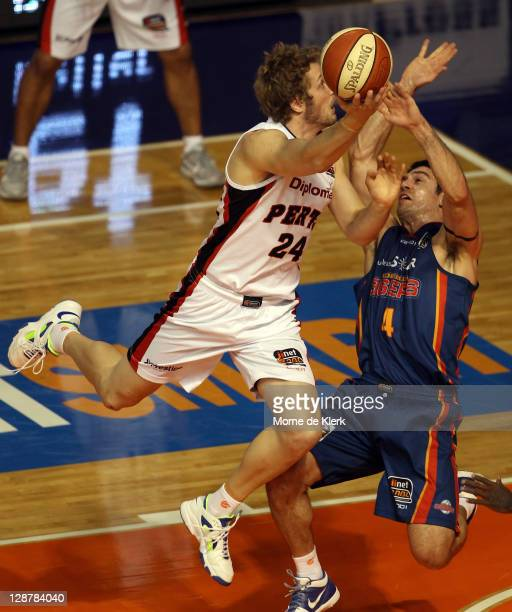 Jesse Wagstaff of the Wildcats runs over Greg Hire of the 36ers during the round one NBL match between the Adelaide 36ers and the Perth Wildcats at...
