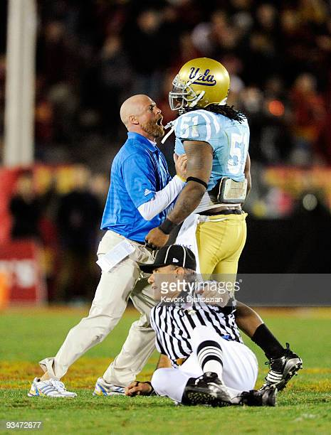 Jesse Ward of the UCLA Bruins is restrained by a team coach as a game offcial falls to the ground during a confrontation with USC Trojans players...