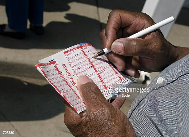 Jesse Warlick from Milwaukee Wisconsin selects numbers for his Big Game lottery picks while standing in line outside a Mobil gas station April 16...