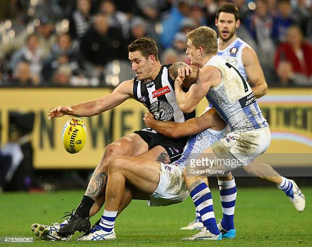 Jesse White of the Magpies is tackled by Robbie Tarrant and Jack Ziebell of the Kangaroos during the round nine AFL match between the Collingwood...