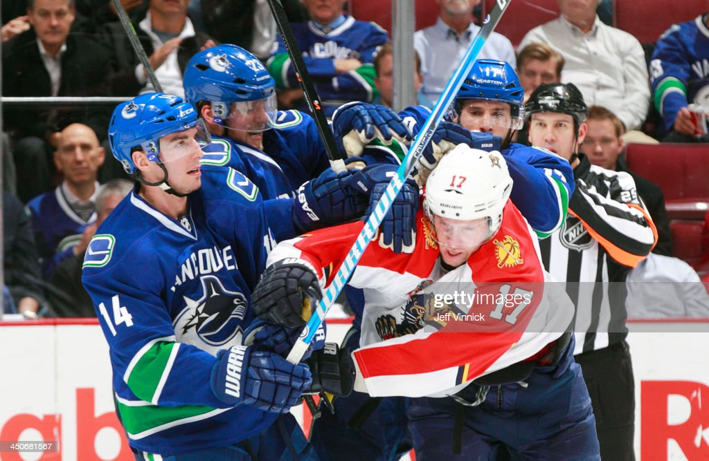 Jesse Winchester #17 of the Florida Panthers draws a crowd of Vancouver Canucks including Alexandre Burrows #14, Alexander Edler #23 and Ryan Kesler #17 during their NHL game at Rogers Arena on November 19, 2013 in Vancouver, British Columbia, Canada. Florida won 3-2 in a shootout.