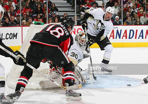 Jesse Winchester of the Ottawa Senators is stopped on a wraparound attempt as Dany Sabourin and Hal Gill of the Pittsburgh Penguins defend at...