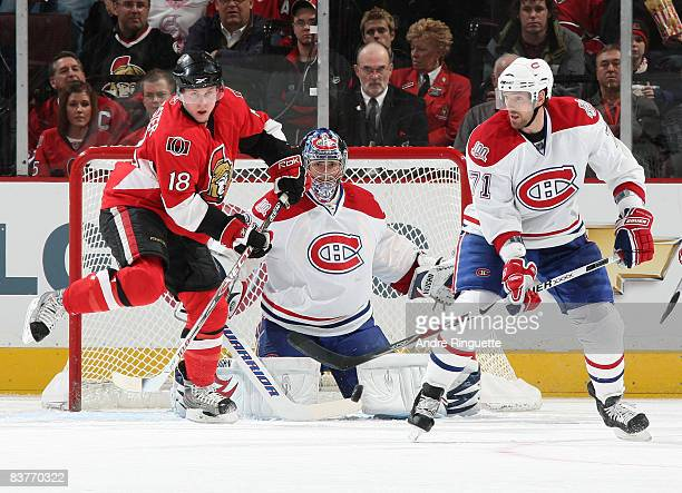 Jesse Winchester of the Ottawa Senators looks to deflect a shot from the point against Carey Price and Patrice Brisebois of the Montreal Canadiens at...