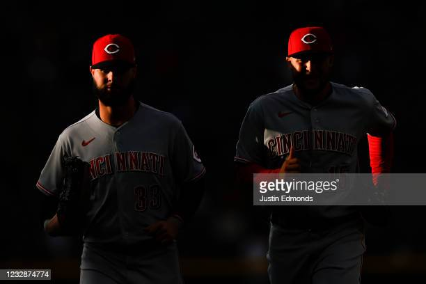 Jesse Winker and Nick Senzel of the Cincinnati Reds jog in from the outfield after the first inning against the Colorado Rockies at Coors Field on...
