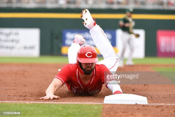 Jesse Winker of the Cincinnati Reds advances to third base on a wild pitch by Mike Fiers of the Oakland Athletics during the third inning of a spring...