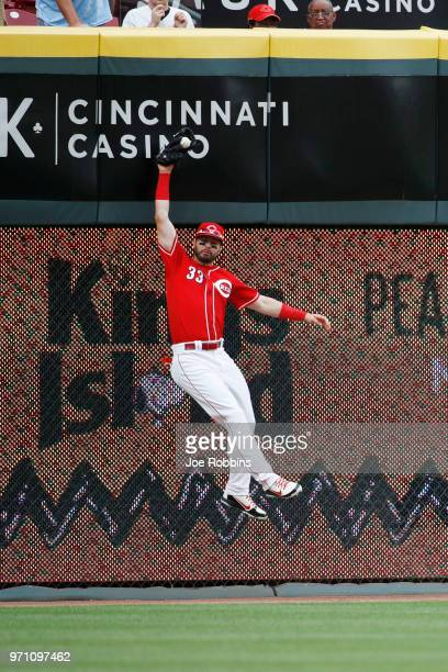 Jesse Winker of the Cincinnati Reds catches the ball at the left field wall but afterwards was ruled a single after replay showed he caught it...