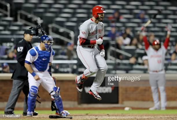 Jesse Winker of the Cincinnati Reds celebrates his game winning home run in the ninth inning as Wilson Ramos of the New York Mets defends at Citi...
