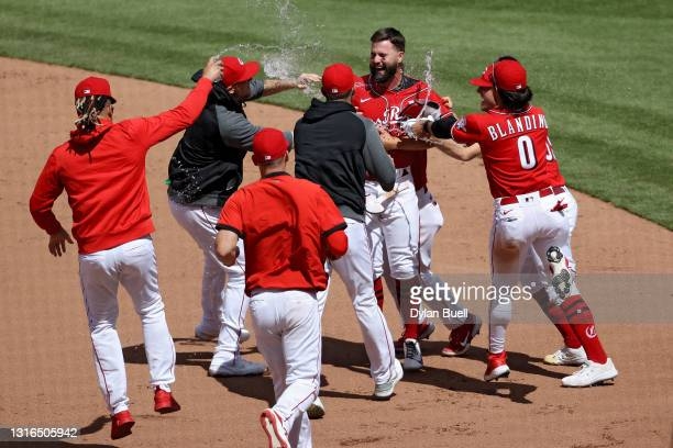 Jesse Winker of the Cincinnati Reds celebrates with teammates after hitting a walk-off single to beat the Chicago White Sox 1-0 in ten innings at...