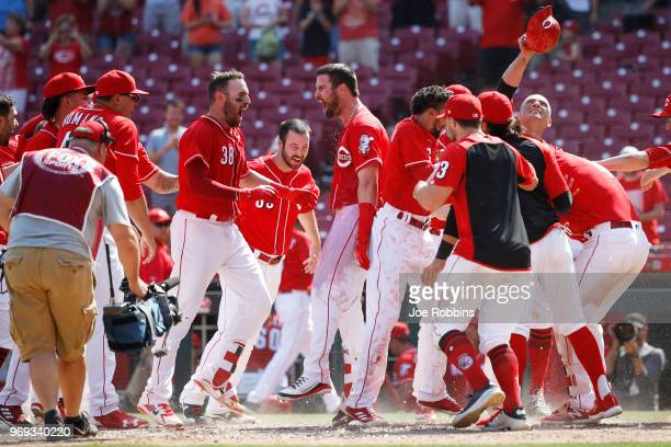 Jesse Winker of the Cincinnati Reds celebrates with teammates after hitting a tworun home run to win the game in the 13th inning against the Colorado...
