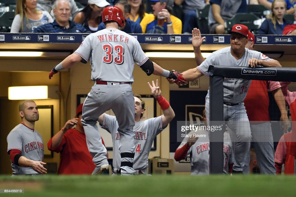 Jesse Winker #33 of the Cincinnati Reds is congratulated by teammates following a solo home run against the Milwaukee Brewers during the eighth inning of a game at Miller Park on September 26, 2017 in Milwaukee, Wisconsin.