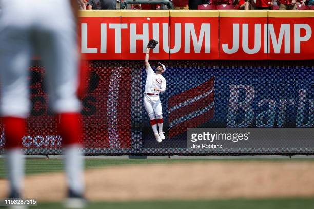 Jesse Winker of the Cincinnati Reds leaps against the left field wall to catch the ball in the sixth inning against the Washington Nationals at Great...