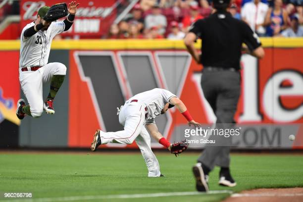 Jesse Winker of the Cincinnati Reds leaps to avoid colliding with Scooter Gennett of the Cincinnati Reds after Gennett was unable to chase down a...