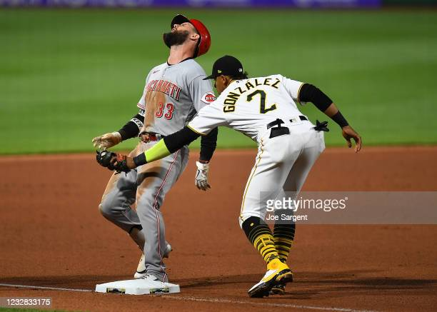 Jesse Winker of the Cincinnati Reds reacts after being tagged out at third base by Erik Gonzalez of the Pittsburgh Pirates during the eighth inning...