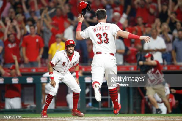 Jesse Winker of the Cincinnati Reds scores the game-winning run as Billy Hamilton looks on after a single by Dilson Herrera in the ninth inning...