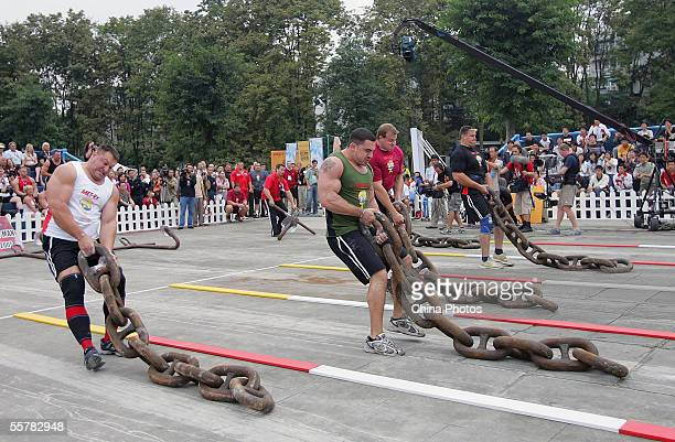 Jessen Paulin of Canada Kevin Nee and Dave Ostlund of USA Janne Virtanen of Finland drag huge iron chains during a match of the 2005 World's...