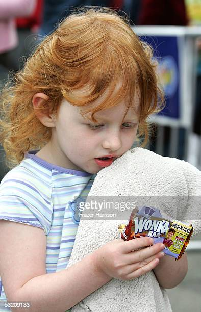 Jessi Dyck samples some Wonka candy during actor Deep Roy's performance dancing on the Charlie and the Chocolate Factory movie billboard in...