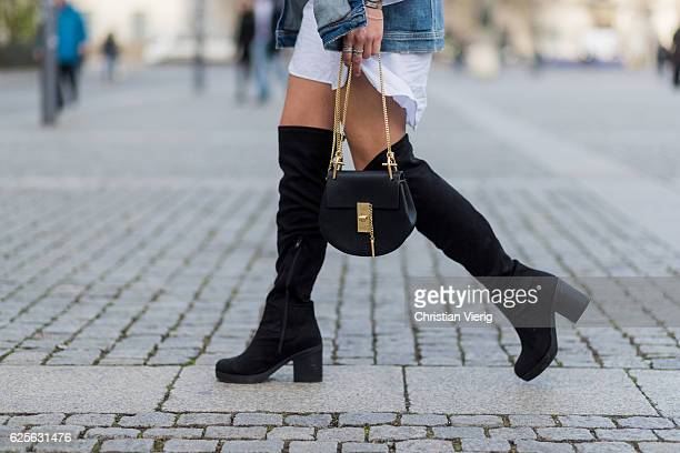 Jessi Quednau wearing black heeled overknees Asos a white dress with long wide sleeves Storets a blue denim jacket with print on the back Mavi a...