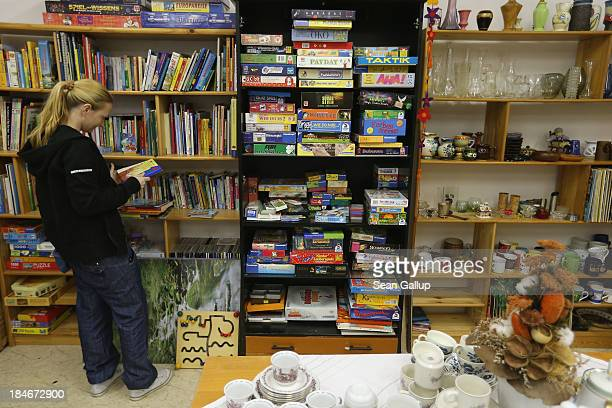 Jessica a mother of two and who only recently began coming to the food bank looks among used children's books for sale at the Falkenseer Tafel food...