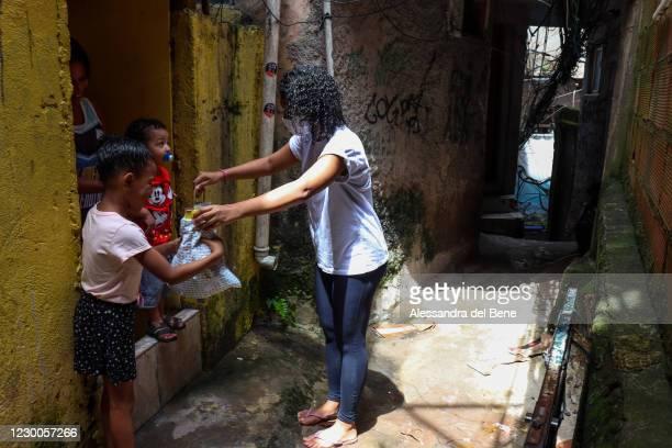 Jessica Albit de Penedo Proenca, a teacher at Uniao de Mulheres Pro Melhoramentos da Roupa Suja Kindergarten, delivers Christmas presents for...