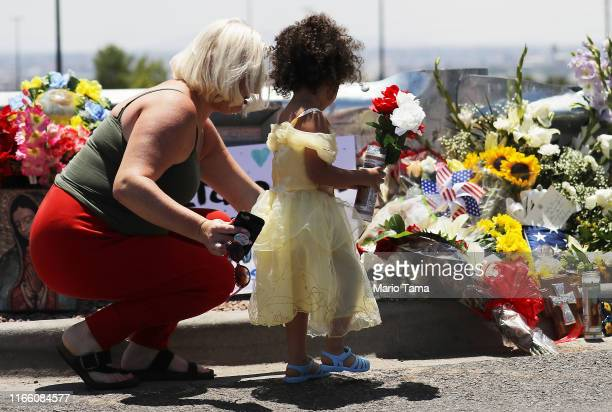 Jessica and Kalani Windham leave flowers and a candle outside Walmart near the scene of a mass shooting which left at least 20 people dead on August...