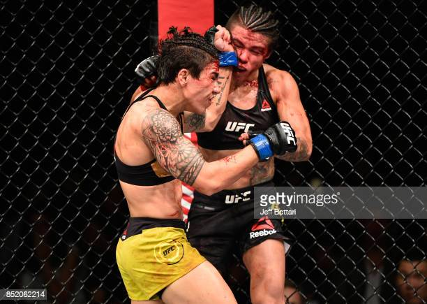 Jessica Andrade of Brazil exchanges punches with Claudia Gadelha of Brazil in their women's strawweight bout during the UFC Fight Night event inside...