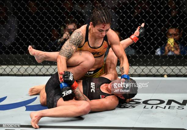 Jessica Andrade of Brazil punches Claudia Gadelha of Brazil in their women's strawweight bout during the UFC Fight Night event inside the Saitama...