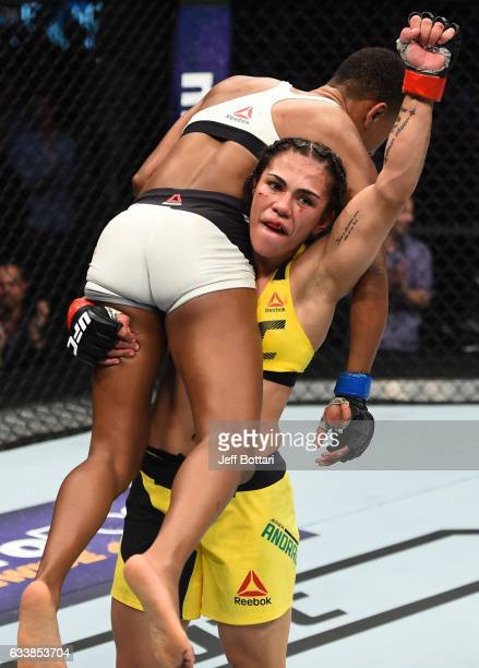 Jessica Andrade of Brazil raises Angela Hill after their women's strawweight bout during the UFC Fight Night event at the Toyota Center on February 4...